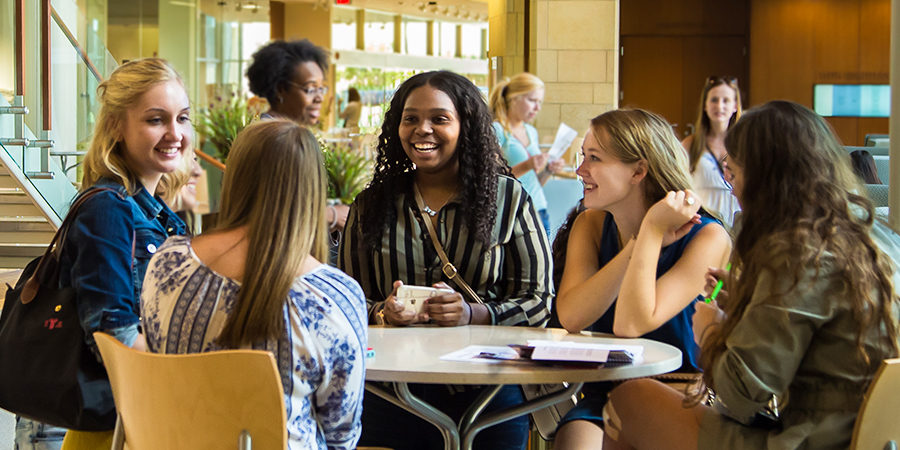 Photo of students laughing together in the Cooper Hall atrium.