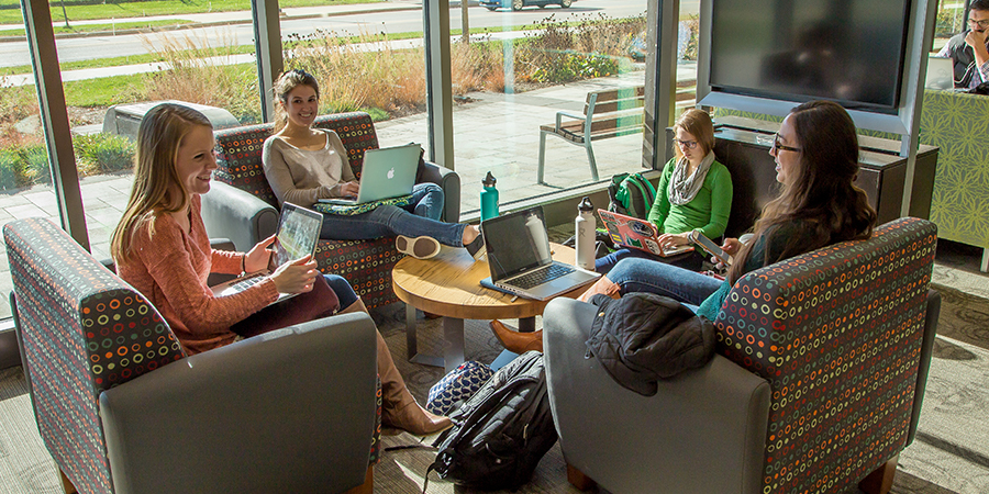 Photo of a group of students laughing and studying by windows in the Curran Commons.