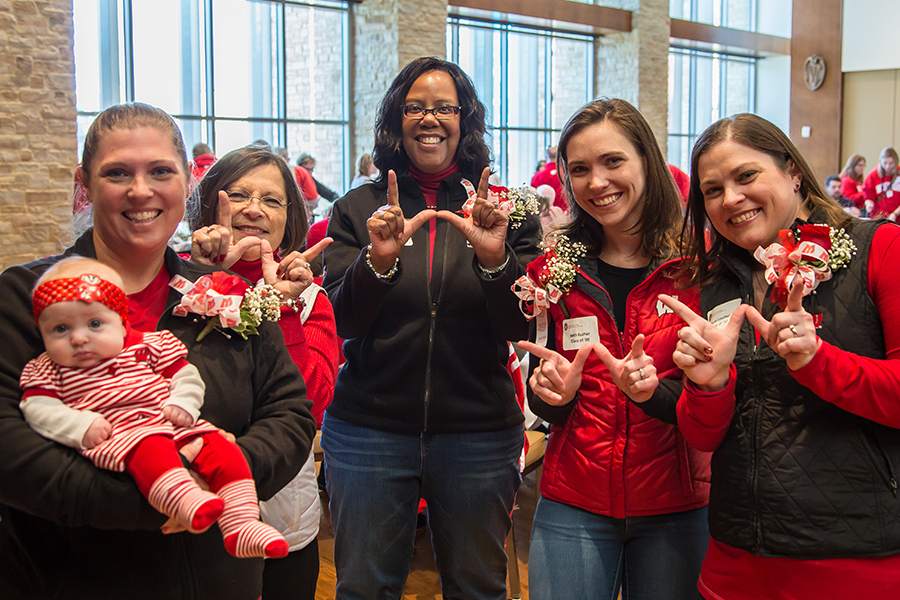 """photo of School of Nursing Dean Linda Scott with School of Nursing alumni dressed in Badger red, making the Wisconsin """"W"""" symbol with their hands"""