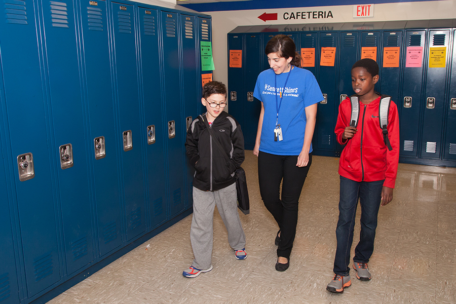 Photo of Sennett Middle School students walk the halls with their school nurse.