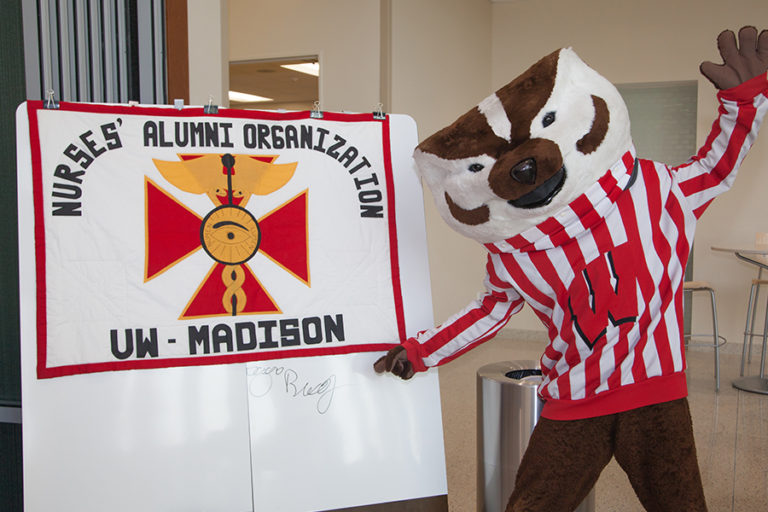 Photo of Bucky Badger posing with the NAO flag.