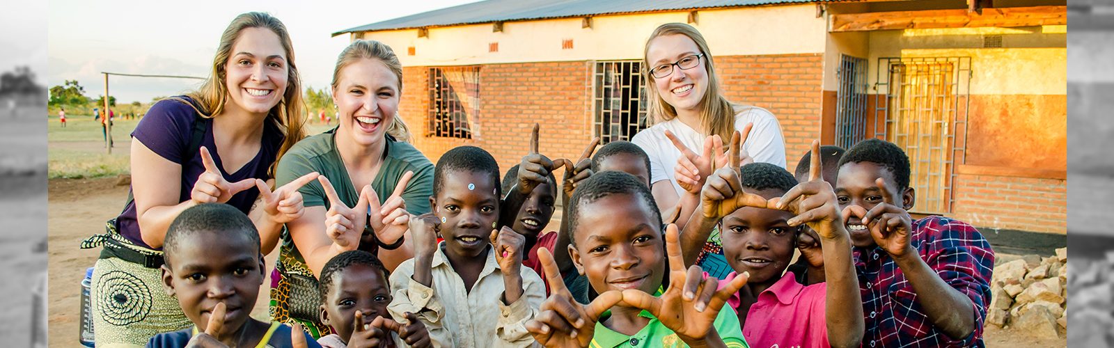 """Student Nurses in Malawi, posing with cute, Malawi children making the """"W"""" symbol with their hands."""