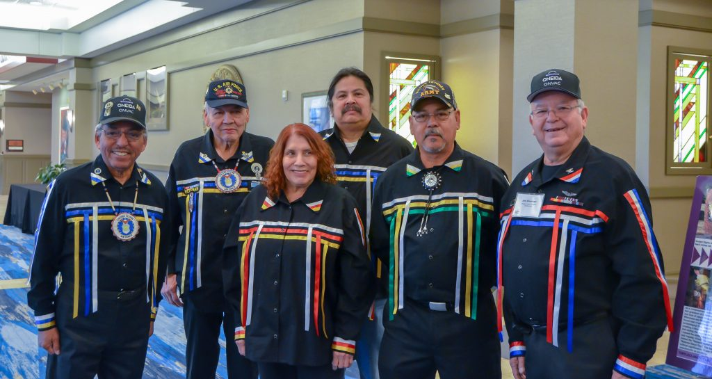 A group of Native American Veterans pose wearing bright colored ribbon shirts