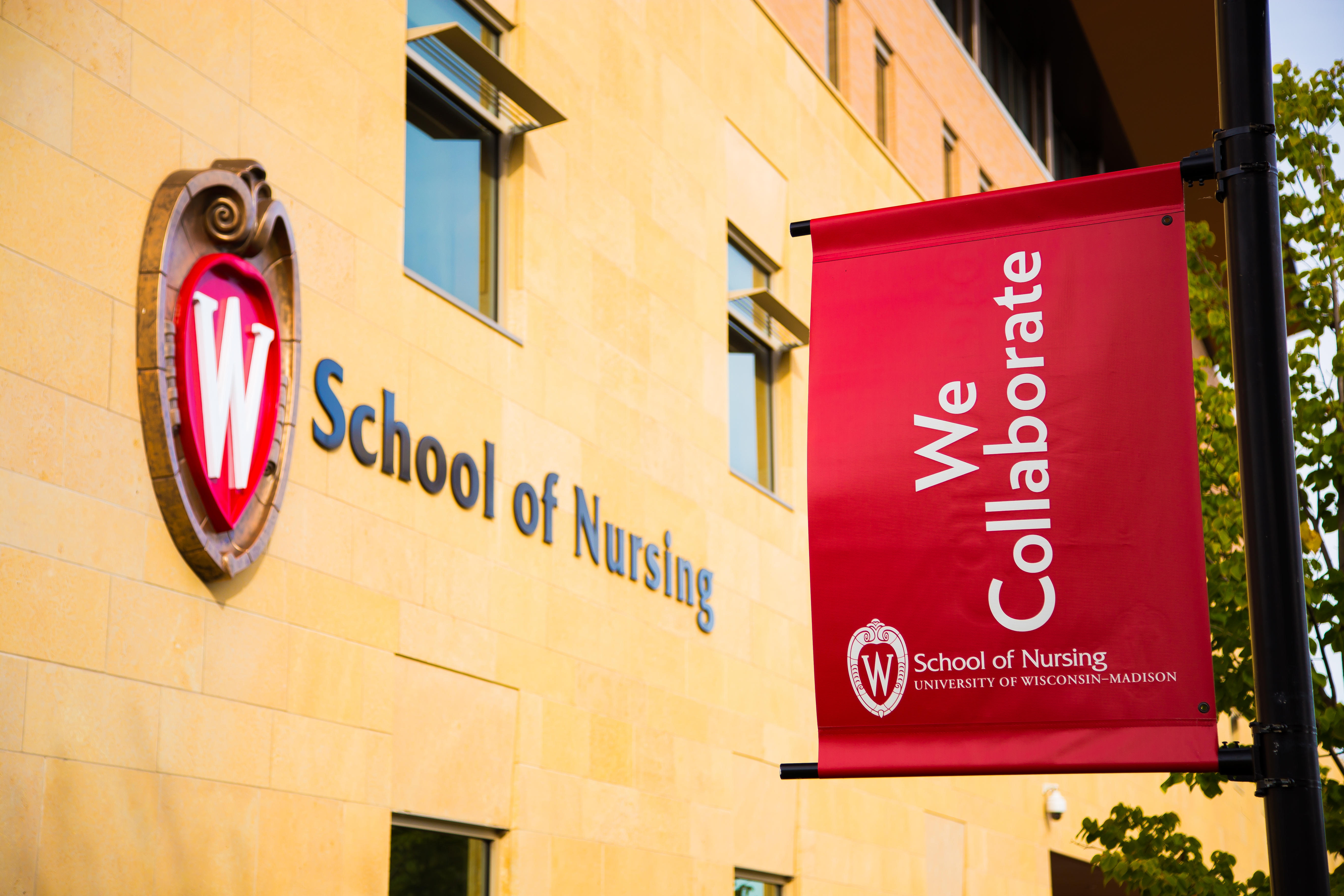 School of Nursing building and light post flag stating--We Collaborate