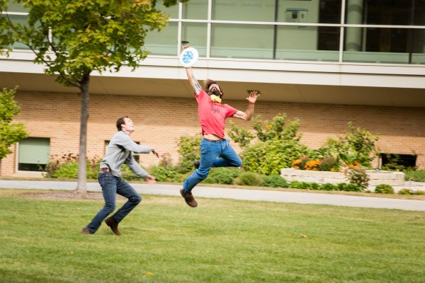 Two students playing frisbee outside