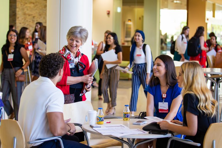 School of Nursing faculty member talks with group of students in Cooper Hall