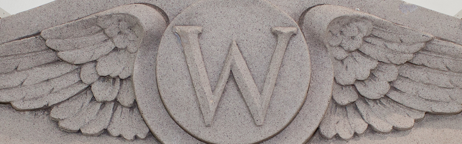 """building stone artifact: the """"Flying W,"""" originally served as a keystone for the main fireplace in the Nurses Dormitory. The Flying W is currently displayed in Signe Skott Cooper Hall, near a shared fireplace in the Curran Commons."""