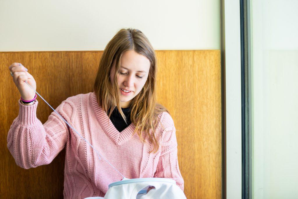 BSN senior Hanna Braaten working on stitch art about nursing